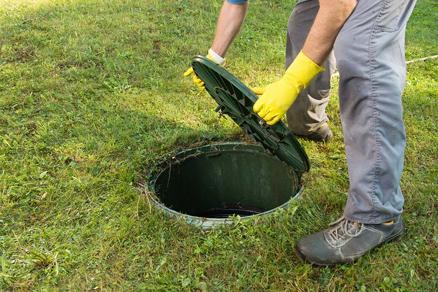 Hands opening septic tank lid