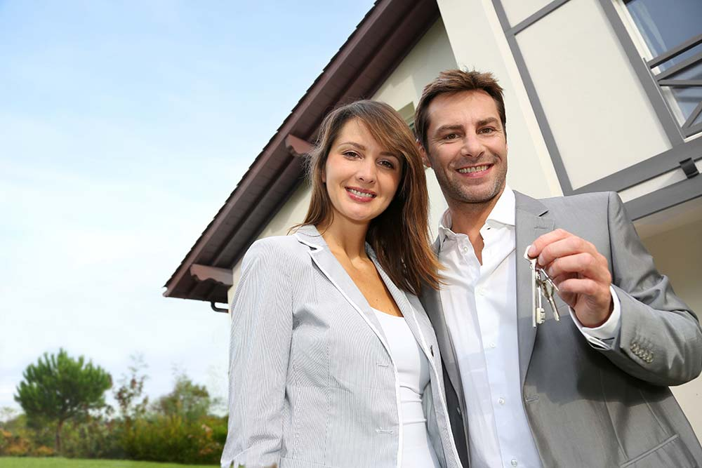 Couple holding the keys to their new house after it passed a thorough home inspection